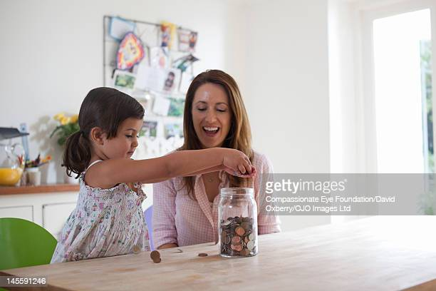mother and daughter (3-4) putting coins into jar - 40 44 jaar stock pictures, royalty-free photos & images