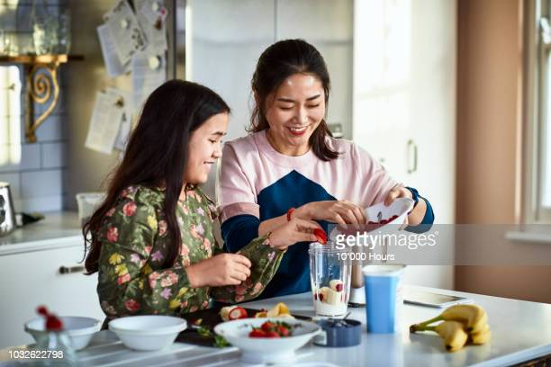 mother and daughter putting fresh strawberries into smoothie maker - stereotypically middle class stock photos and pictures