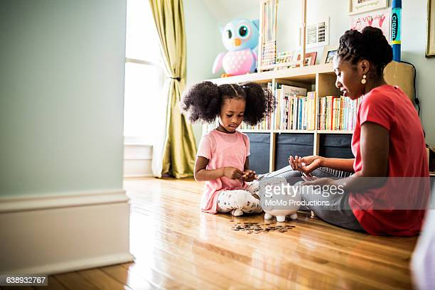 mother and daughter putting money in piggybank