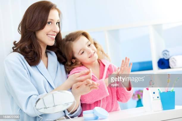 Mãe e filha na mão colocando creme Hidratante