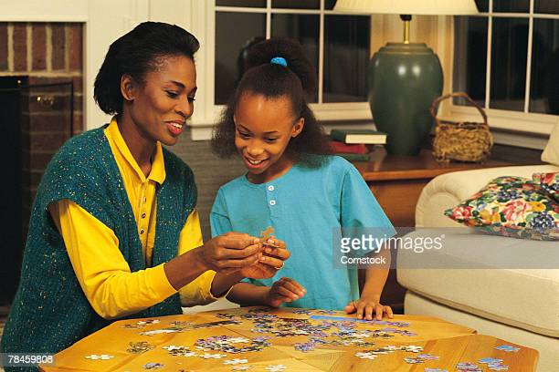 Mother and daughter putting together puzzle