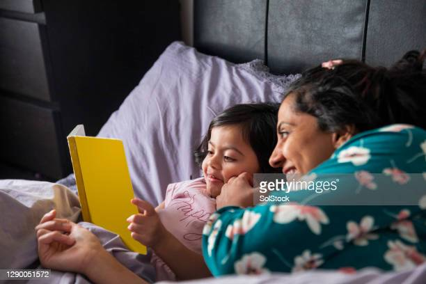 mother and daughter reading a book in bed - reading stock pictures, royalty-free photos & images
