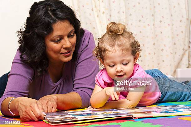 mother and daughter reading a book. - baby pointing stock photos and pictures
