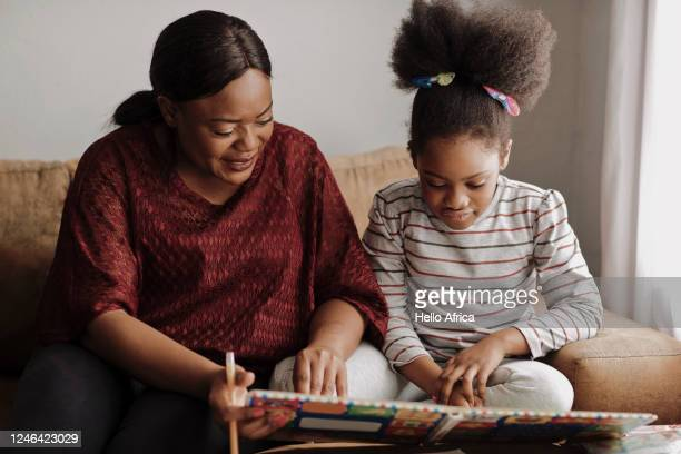 mother and daughter reading a children's book on the couch - education stock pictures, royalty-free photos & images