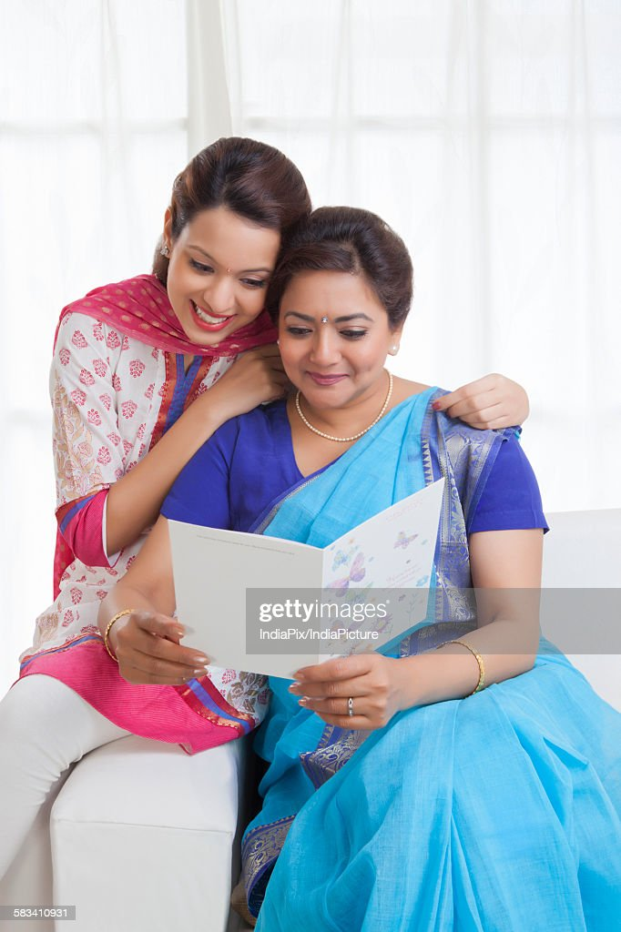 Mother and daughter reading a greeting card : Stock Photo