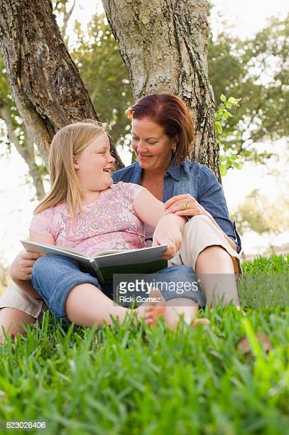 Mother and daughter (7-9) reading book in park