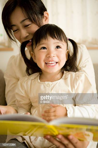 Mother and daughter reading book.
