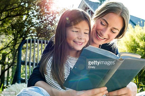 mother and daughter reading book - 6 7 jaar stockfoto's en -beelden