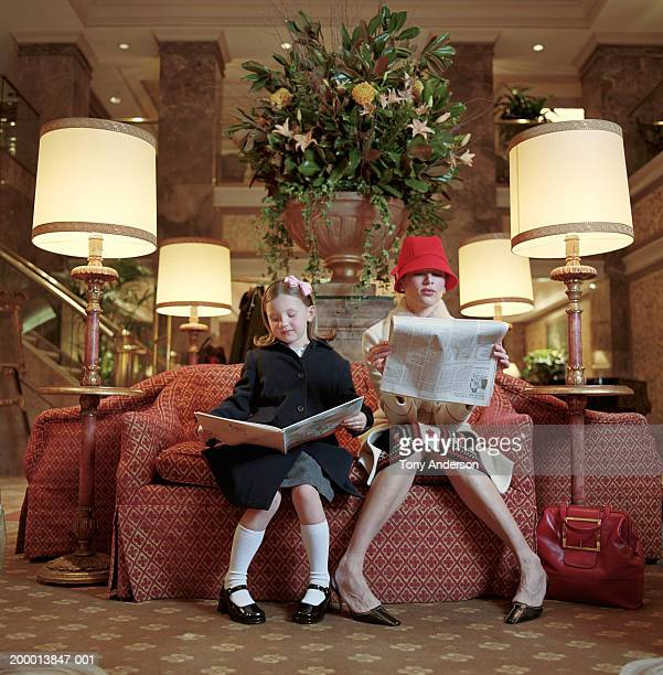 Mother and daughter (5-7) reading in hotel lobby