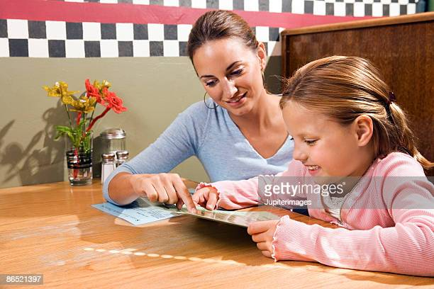 Mother and daughter reading menu at restaurant