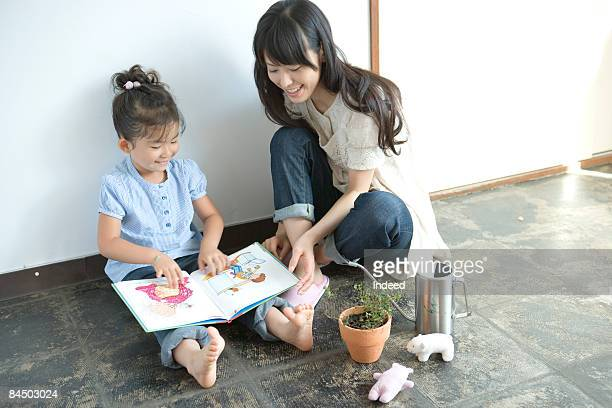 Mother and daughter reading picture book on floor