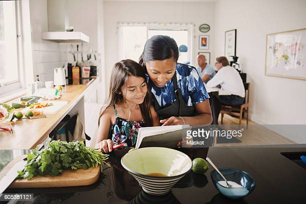 Mother and daughter reading recipe book while cooking in kitchen