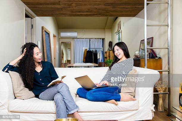 mother and daughter relaxing at home on the sofa. - tdub_video stock pictures, royalty-free photos & images