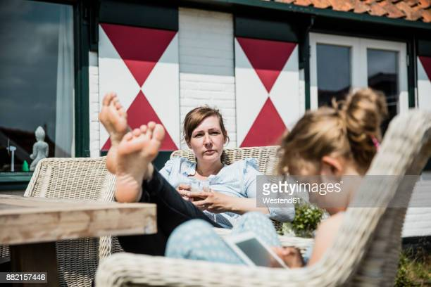 Mother and daughter relaxing at terrace table