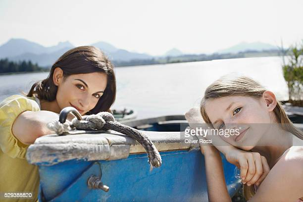 Mother and daughter relaxing by lake