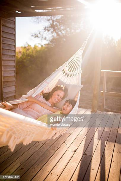 Mother and daughter relaxing in a hammock with sun flare