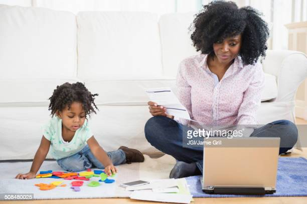 mother and daughter relaxing in living room - fun calculator stock photos and pictures