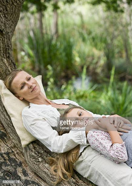Mother and daughter relaxing on a tree root