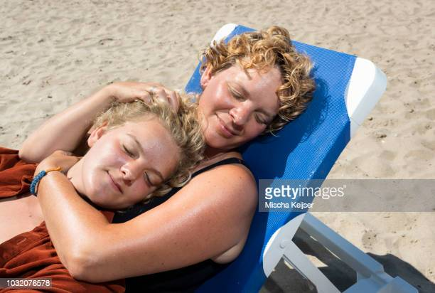 Mother and daughter relaxing on beach