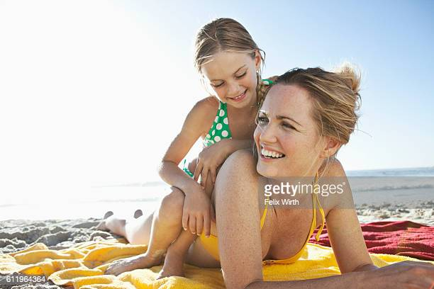 Mother and daughter (10-12) relaxing on beach