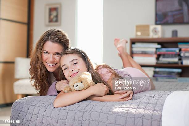 mother and daughter relaxing on bed - barefoot feet up lying down girl stock photos and pictures