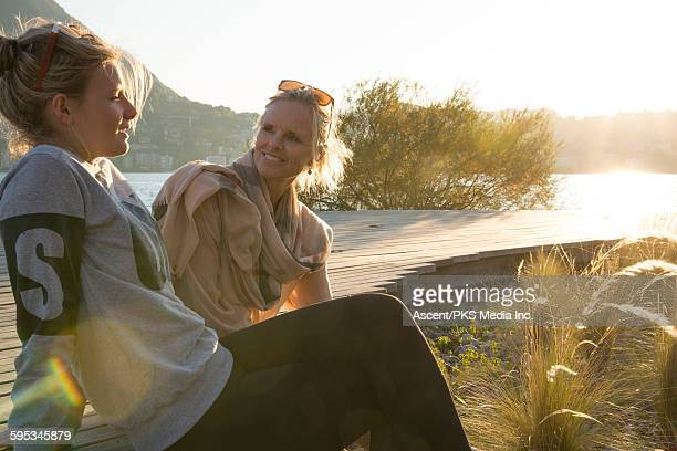 Mother and daughter rest on boardwalk,by lakeshore