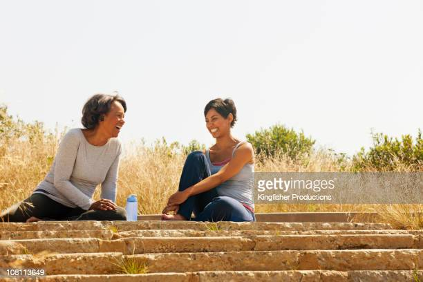 Mother and daughter resting after exercise outdoors