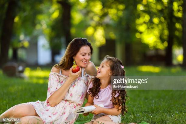 Mother and daughter resting in park reading a book