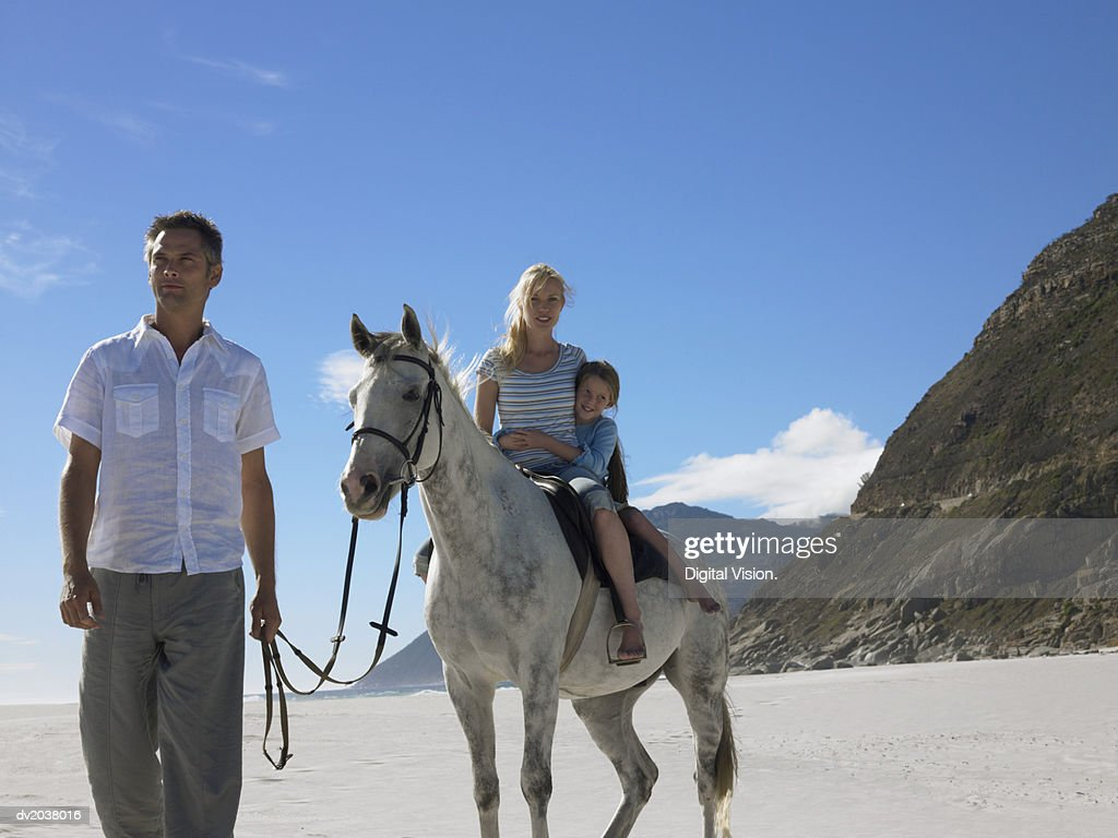 Mother and Daughter Riding a White Horse on the Beach With the Father Holding the Reins : Stock Photo