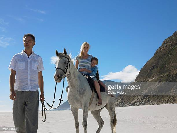 Mother and Daughter Riding a White Horse on the Beach With the Father Holding the Reins