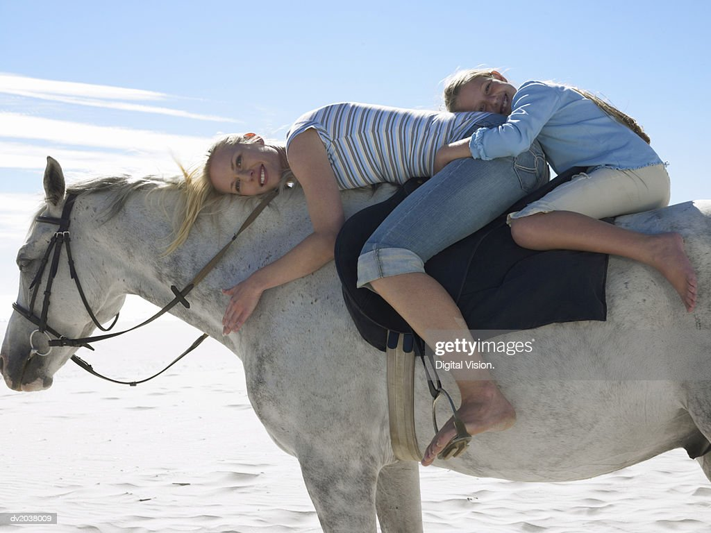 Mother and Daughter Riding a White Horse : Stock Photo