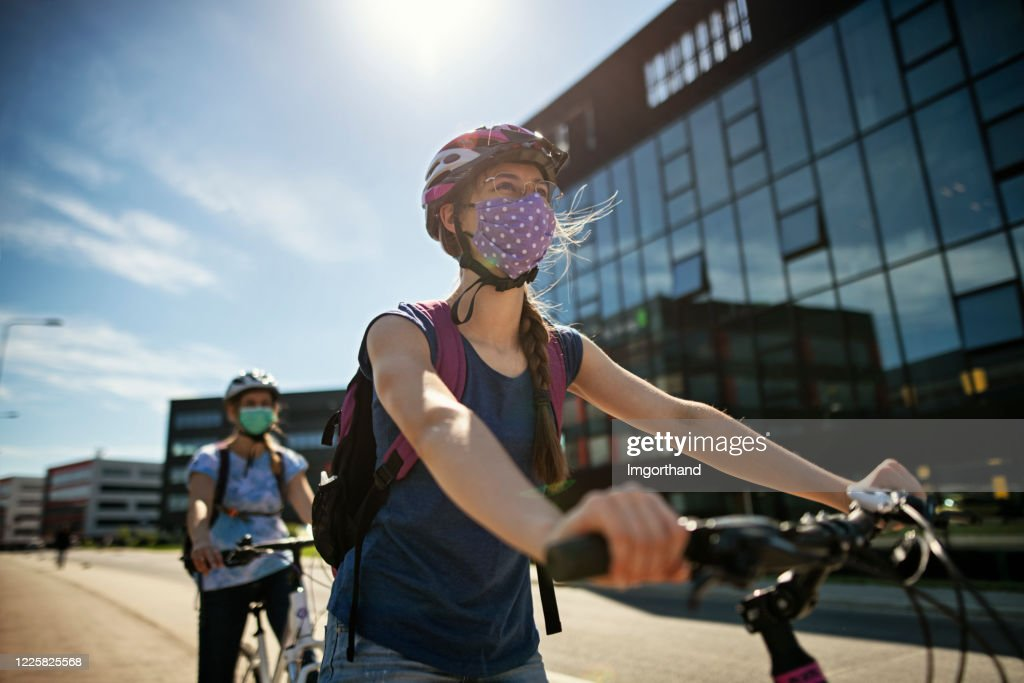Mother and daughter riding bikes during Covid-19 pandemic : Stock Photo