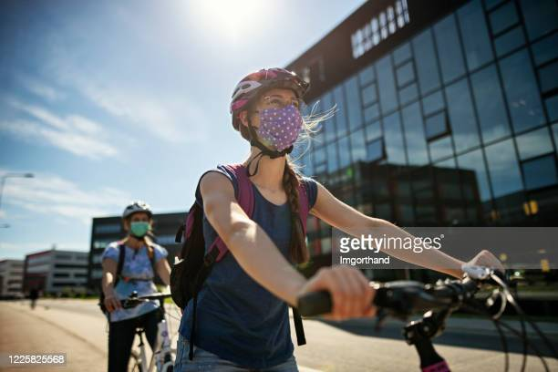 mother and daughter riding bikes during covid-19 pandemic - riding stock pictures, royalty-free photos & images