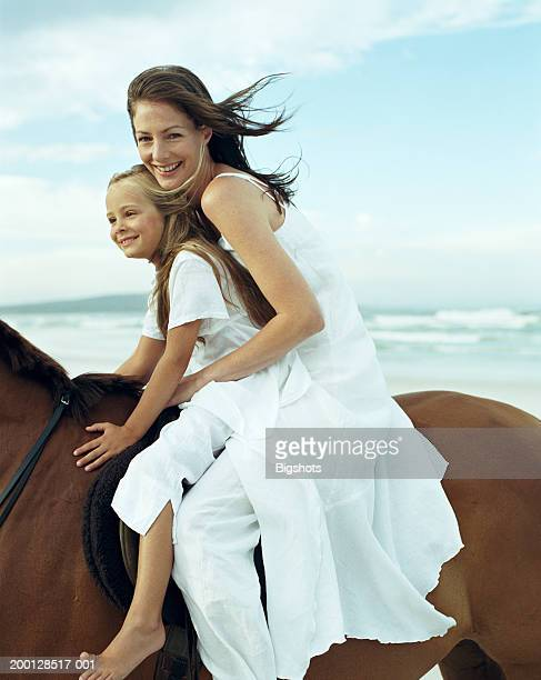 Mother and daughter (5-7) riding horse on beach, portrait