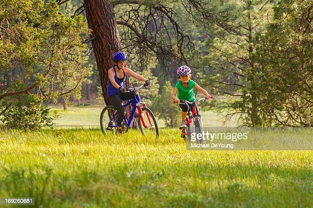 Mother and daughter riding mountain bikes in meadow