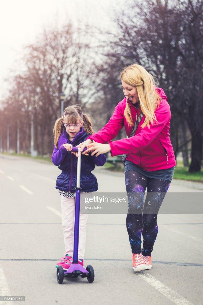 Moeder en dochter rijden op een push-scooter : Stockfoto