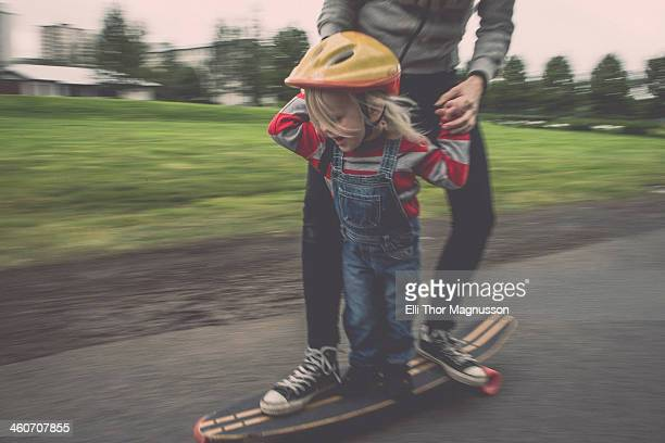 mother and daughter riding on skateboard in park - sports helmet stock pictures, royalty-free photos & images