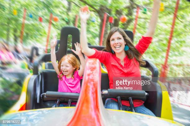 Mother and daughter riding roller coaster in amusement park