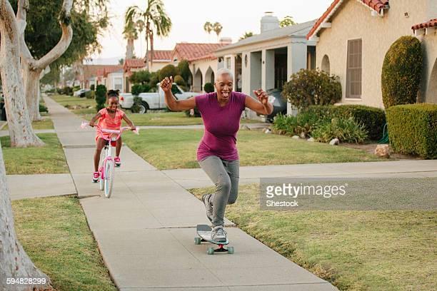 mother and daughter riding skateboard and bicycle on sidewalk - rijden activiteit stockfoto's en -beelden