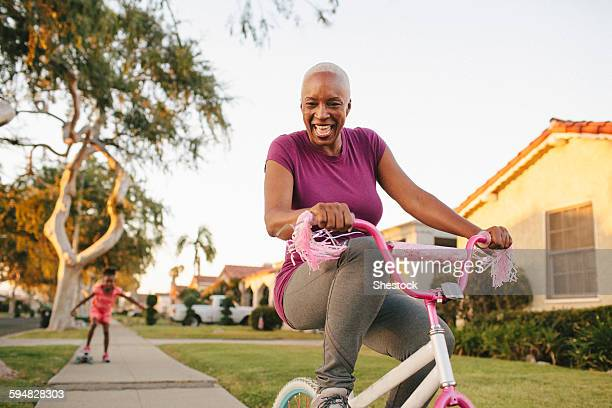 mother and daughter riding skateboard and bicycle - disruptaging foto e immagini stock
