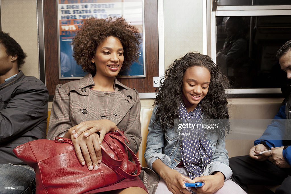Mother and daughter riding subway : Stock Photo