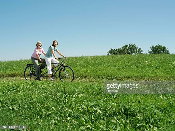 Mother and daughter (16-17) riding tandem bicycle in meadow