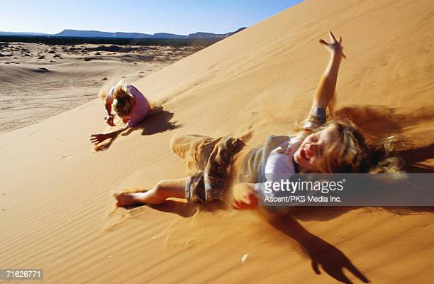 mother and daughter rolling down sand dunes, coral pink sand dunes state park, united states of america - sandy utah stock pictures, royalty-free photos & images
