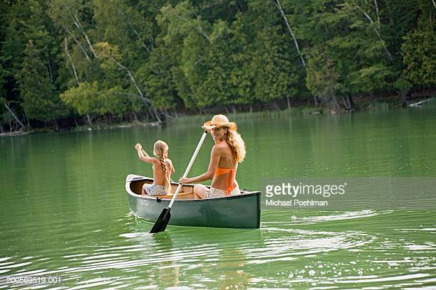 Mother and daughter (8-9) rowing fishing boat