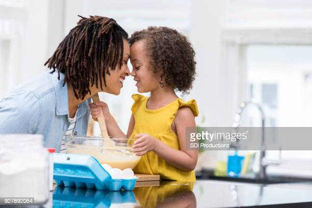 Mother and daughter rub noses while baking together