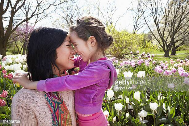 Mother and daughter rubbing noses in park