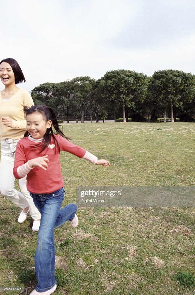 Mother and Daughter Running in a Park : Stock Photo
