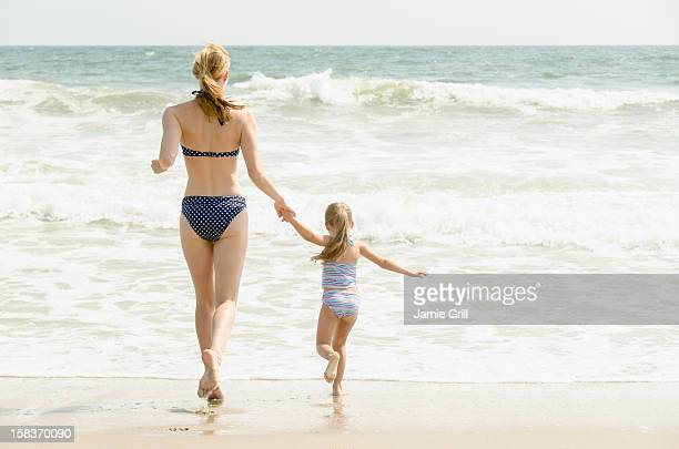 mother and daughter running into ocean together - rockaway peninsula stock pictures, royalty-free photos & images