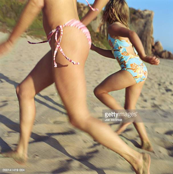 mother and daughter (9-11) running on beach (blurred motion) - bikini bottom stock pictures, royalty-free photos & images