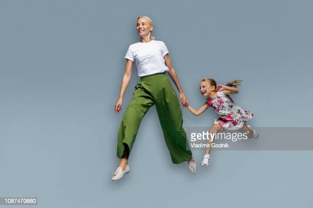 mother and daughter running on blue background - in der luft schwebend stock-fotos und bilder
